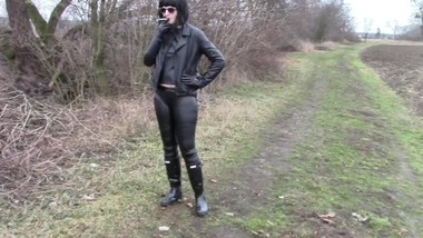 Smoking cigarettes in a leather outfit, wellies and handcuffs