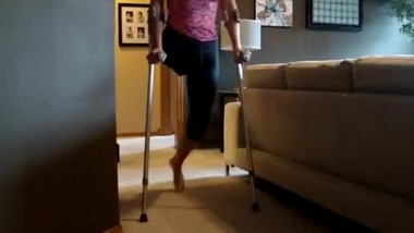 Barefoot Amputee Woman Practices Using Crutches and a Walker