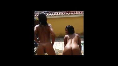Latinas expoing on rooftop swimming pool