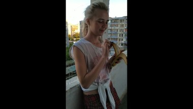 Young sexy blonde eating a banana