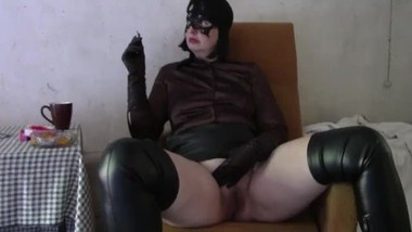 Mistress smokes in leather gloves and boots