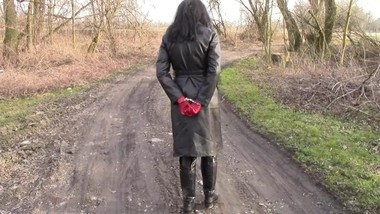 A small walk in a leather coat and with handcuffs